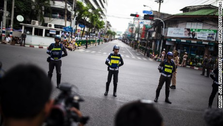 Bangkok police stand watch before King Bhumibol's funeral procession.