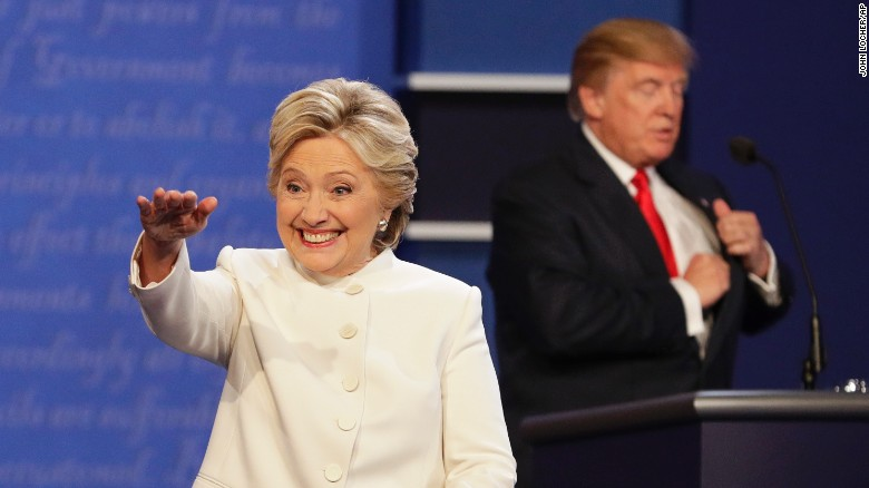 Democratic presidential nominee Hillary Clinton waves to the audience as Republican presidential nominee Donald Trump puts away his notes after the third presidential debate at UNLV in Las Vegas, Wednesday, Oct. 19, 2016. (AP Photo/John Locher)