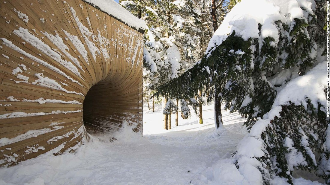 This serene residence features a curved tunnel at its entrance, which is made from bent planks of raw larch wood. The tunnel appears like a wooden vortex hidden behind trees.