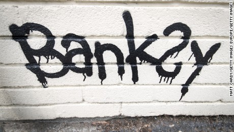 BRISTOL, ENGLAND - JUNE 07:  The name Banksy is written left as part of a mural which was painted on the side of one of the classrooms at Bridge Farm Primary in Bristol during half-term on June 7, 2016 in Bristol, England. The 14ft piece, showing a child with a stick chasing a burning tyre, was discovered at the school yesterday morning along with a letter to the caretaker and was said to be a thank you by the elusive artist after the school recently named a house after him.  (Photo by Matt Cardy/Getty Images)