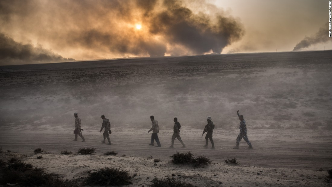 Iraqi soldiers travel along a road near Qayyara as clouds of black smoke rise in the sky on Wednesday, October 19.
