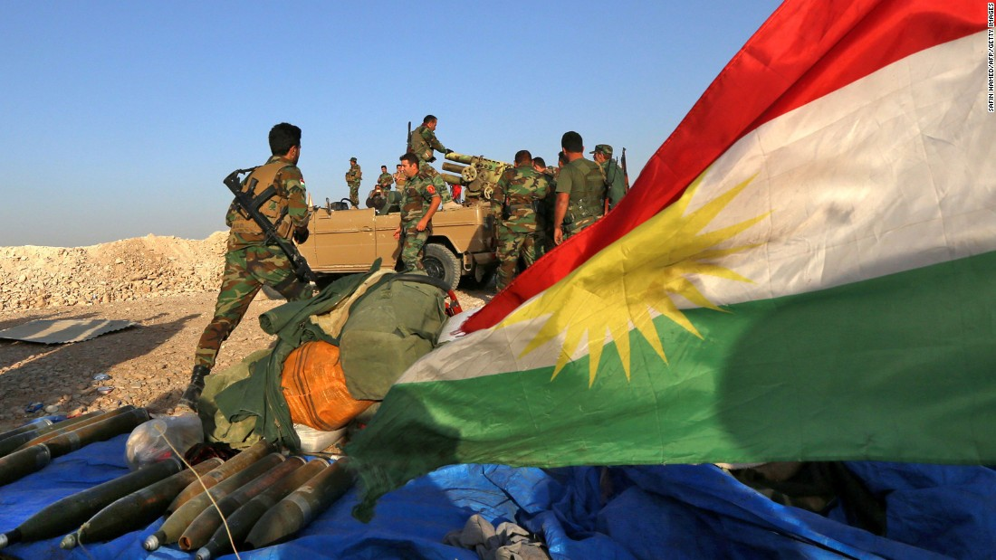 A flag flies as Peshmerga fighters prepare to fire a rocket near Bashiqa on October 20.