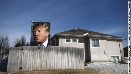 A giant poster of Republican presidential candidate Donald Trump stands in the backyard of a supporter in West Des Moines, Iowa.