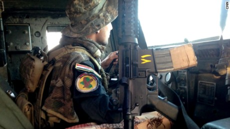 An Iraqi special forces soldier looks for danger as he drives to the front lines of Bartella.