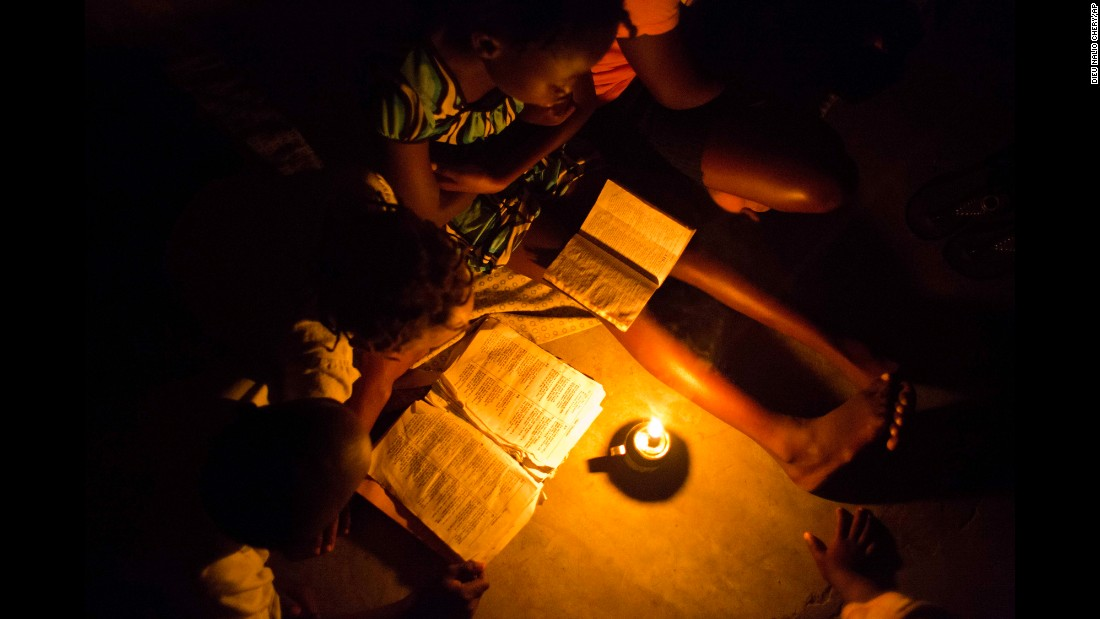 "A 12-year-old girl reads the Bible in her school's classroom in Les Cayes, Haiti, on Sunday, October 16. She and other locals took refuge in the school after <a href=""http://www.cnn.com/2016/10/03/world/gallery/hurricane-matthew/index.html"" target=""_blank"">Hurricane Matthew</a> destroyed their homes in the village of Mersan."