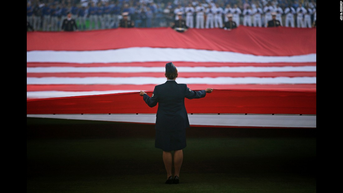 Military personnel carry an American flag before Game 3 of the National League Championship Series on Tuesday, October 18.