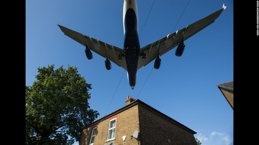 A passenger jet passes over a house as it prepares to land at London's Heathrow Airport on Monday, October 17. The British government is considering whether to approve a third runway at Heathrow.