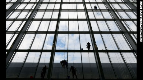 "TOPSHOT - Workers clean the windows of the new Convention center named ""The cloud"" (""La Nuvola"" in Italian) designed by Italian architect Massimiliano Fuksas on October 19, 2016 in the Eur business district in Rome. The congress center will be inaugurated on October 29, 2016.  