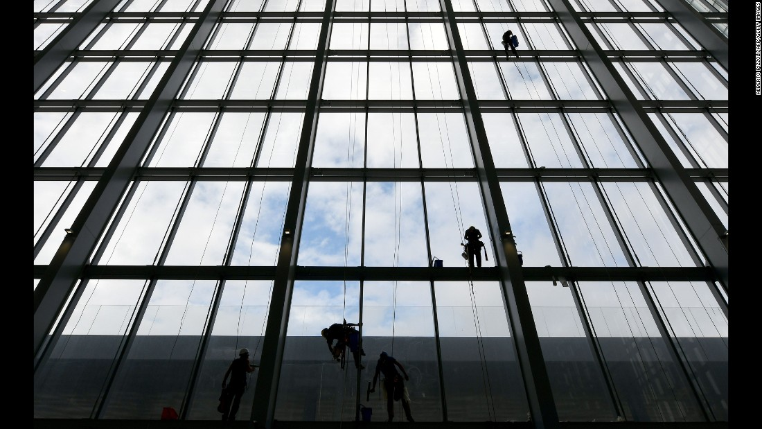 "Workers clean the windows of ""The Cloud,"" a new convention center in Rome on Wednesday, October 19."