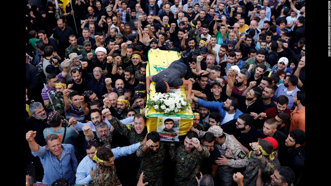 People in Beirut, Lebanon, carry the coffin of Hatem Hamadi, a Hezbollah commander killed in Syria, on Tuesday, October 18.