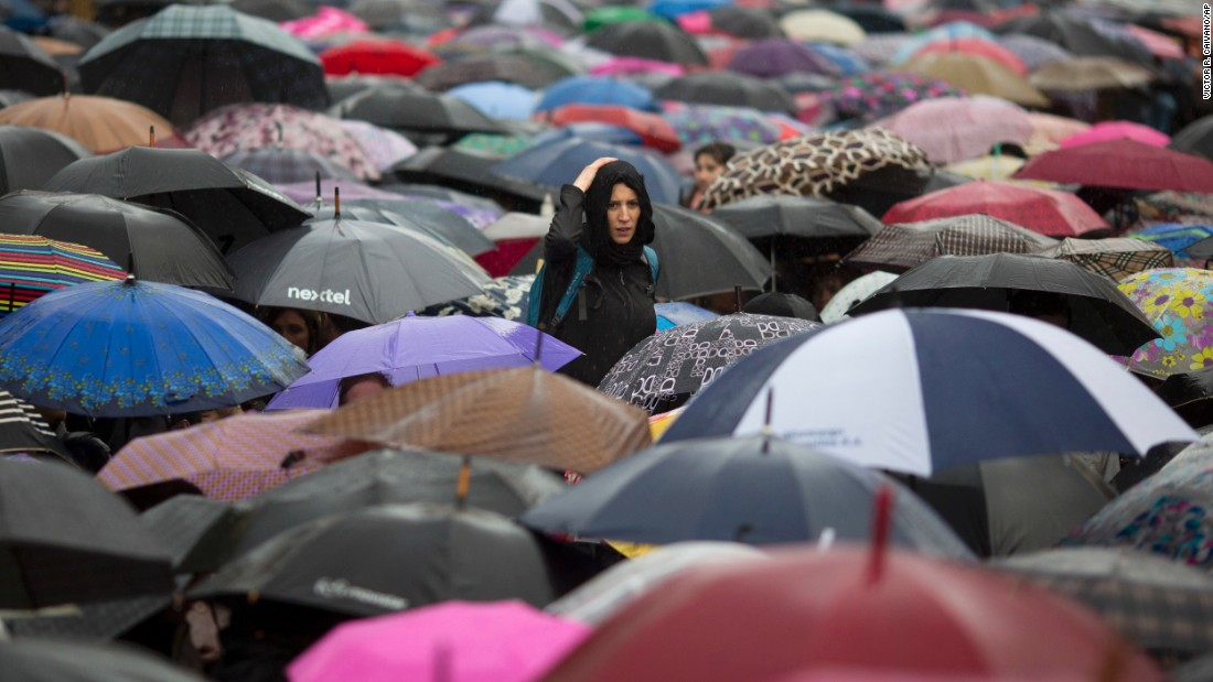 "A woman looks over protesters with umbrellas during a demonstration in Buenos Aires on Wednesday, October 19. Thousands of people wearing black clothes braved torrential rain to protest the rape and killing of 16-year-old Lucia Perez, who was abducted outside her school in Mar del Plata on October 8. Protesters called the protest <a href=""http://www.cnn.com/2016/10/20/americas/argentina-teen-raped-killed-trnd/"" target=""_blank"">Black Wednesday</a> and turned it into a day to demand an end to violence against women nationwide."