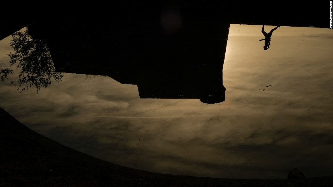 A runner is reflected on a pond in Pamplona, Spain, on Wednesday, October 19.