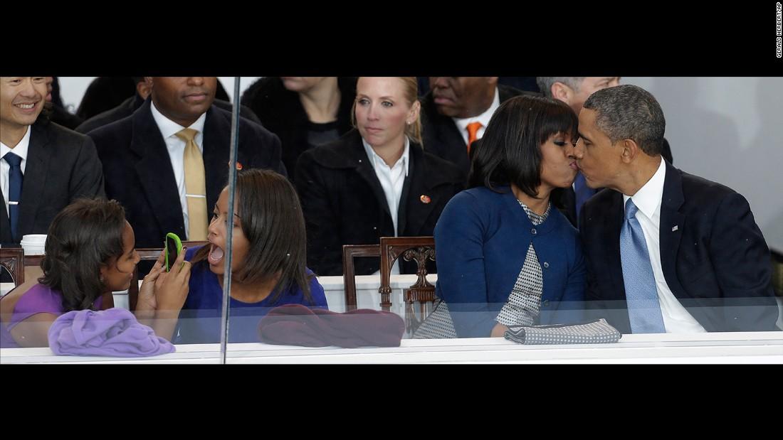 Obama kisses his wife during the inaugural parade in Washington. Sasha, left, takes a photo of her sister, Malia.