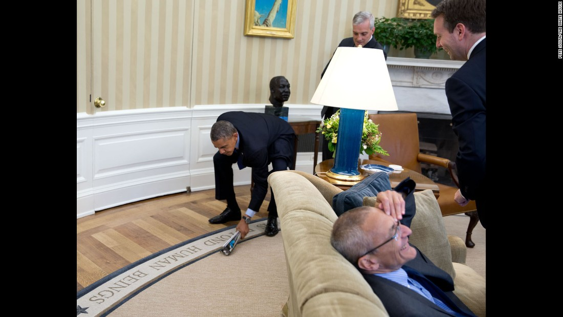 Aides laugh as the President swats a fly in the Oval Office on May 6, 2014.