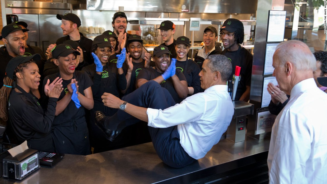 "Obama slides across a counter to pose with staff members at a Shake Shack restaurant in Washington on May 16, 2014. Vice President Joe Biden, lower right, also did the same. ""The President normally does a group photo with restaurant staff when he stops for lunch or dinner,"" White House Photographer Pete Souza said."
