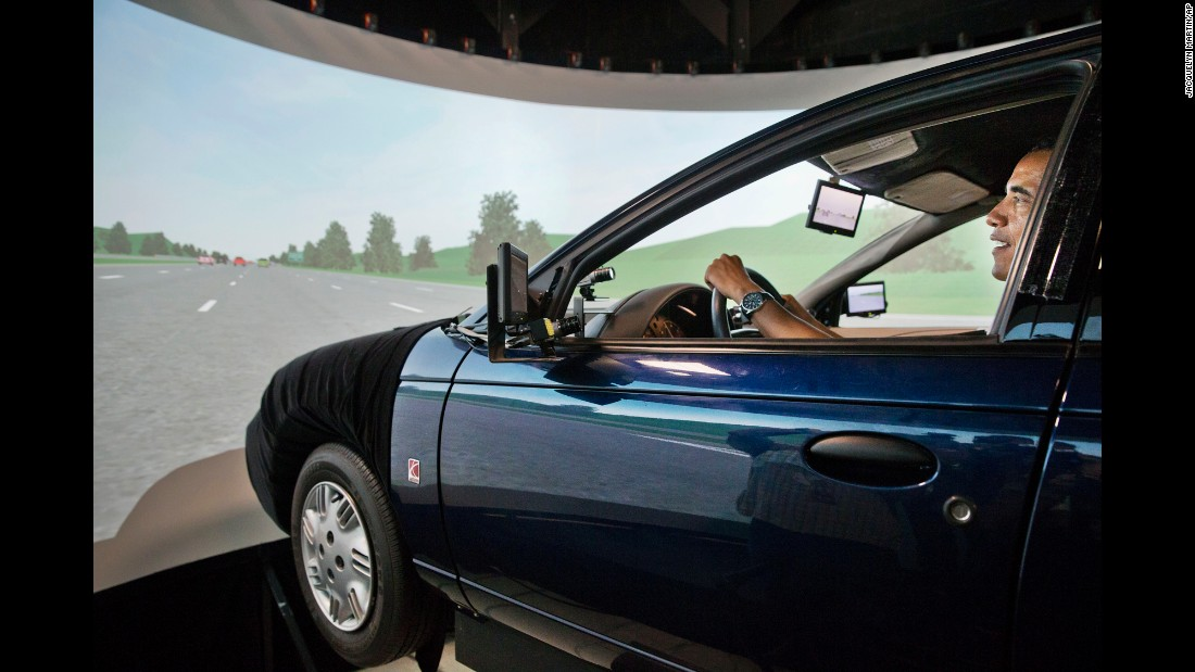 "Obama tries out a driving simulator July 15, 2014, as he tours the Turner-Fairbank Highway Research Center in McLean, Virginia. The simulator was meant to demonstrate the types of ""smart"" vehicles being developed at the center."