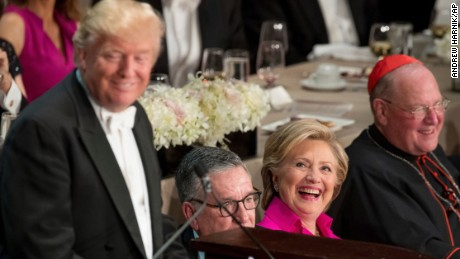 Republican presidential candidate Donald Trump, left, accompanied by Democratic presidential candidate Hillary Clinton, second from right, and Cardinal Timothy Dolan, Archbishop of New York, right, speaks at the 71st annual Alfred E. Smith Memorial Foundation Dinner, a charity gala organized by the Archdiocese of New York, Thursday, Oct. 20, 2016, at the Waldorf Astoria hotel in New York. (AP Photo/Andrew Harnik)