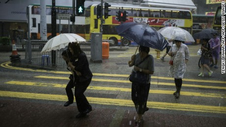 As Typhoon Haima edged closer, pedestrians walk with umbrellas during a heavy downpour in Hong Kong's Causeway Bay district on October 19, 2016.