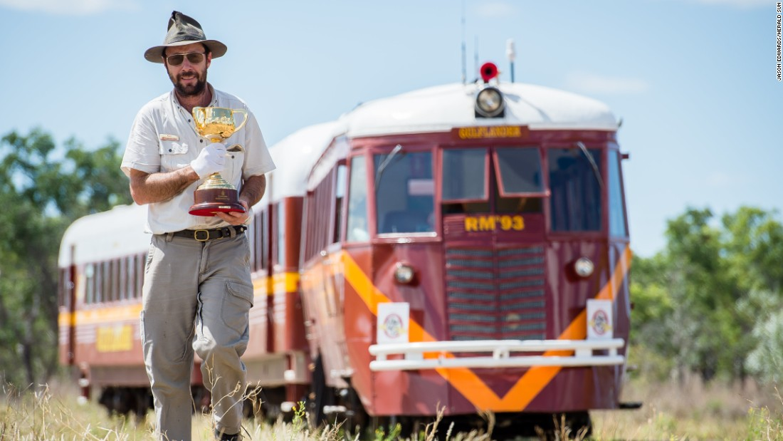 Train driver Ken Fairbairn with the Cup in front of the Gulflander train outside Croydon, outback Queensland.