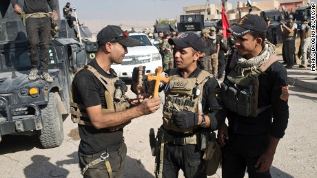 Iraqi Special Forces soldiers hold a cross found in the town of Bartella on Saturday