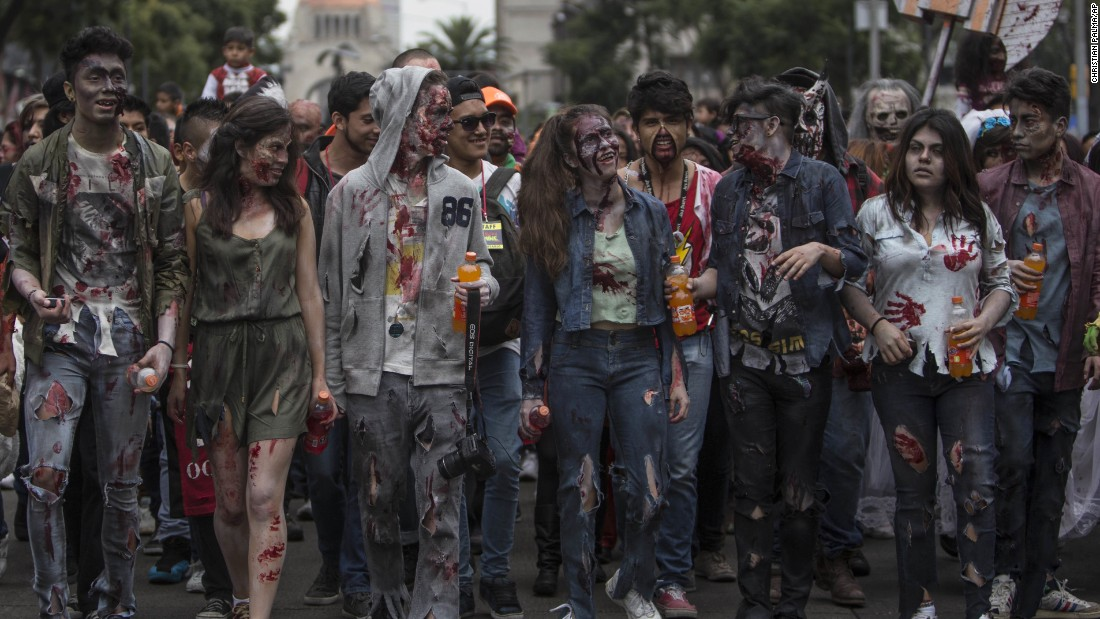 People dressed in rags and ghoulish makeup take part in the annual Zombie Walk in Mexico City on Saturday, October 22.