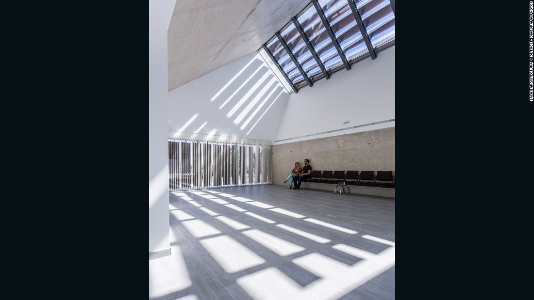 The concrete building features windows that cast shadows across the room, which move as the day goes on to symbolize the passage of time. <br />