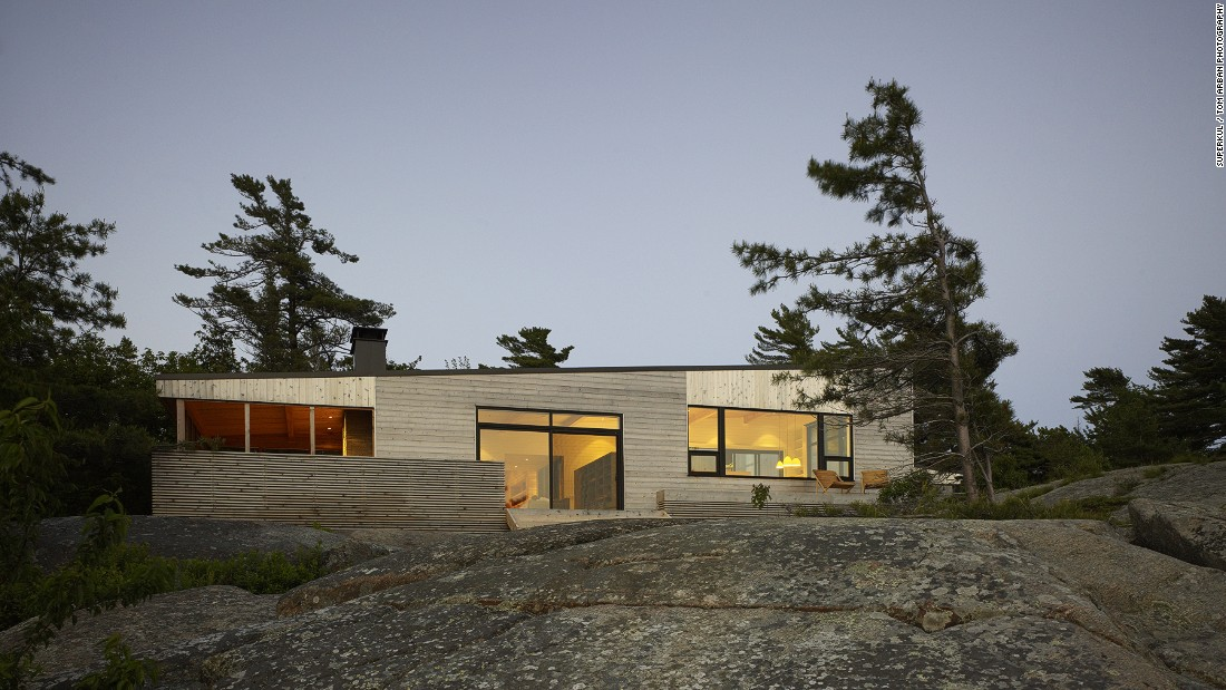 Superkül architects' Shift Cottage sits on the shore of Georgian Bay in Ontario, Canada. The cottage's windows overlook a row of conifer trees, and a cedar deck offers ample outdoor living space.