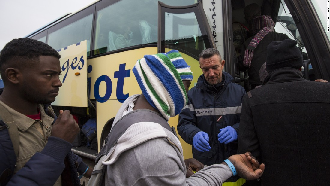Migrants board buses that will transport them to shelters around France on October 24. Those applying for asylum will be offered temporary accommodation in a shelter while their claim is processed.