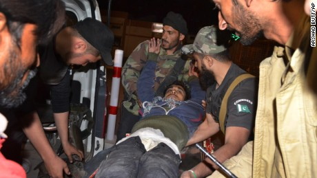 Pakistani volunteers and police officers rush an injured person to a hospital in Quetta, Pakistan, Monday, October 24, 2016, after two separate attacks in Pakistan.  Gunmen stormed a police training center in the restive southwestern province of Baluchistan Monday, leaving several people wounded, hours after another attack near to Quetta leaving two customs officers dead, authorities said.