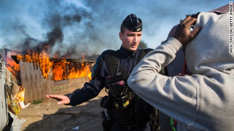 A police officer stands guard after migrants burn down a shelter as authorities move in to clear the camp on Tuesday.