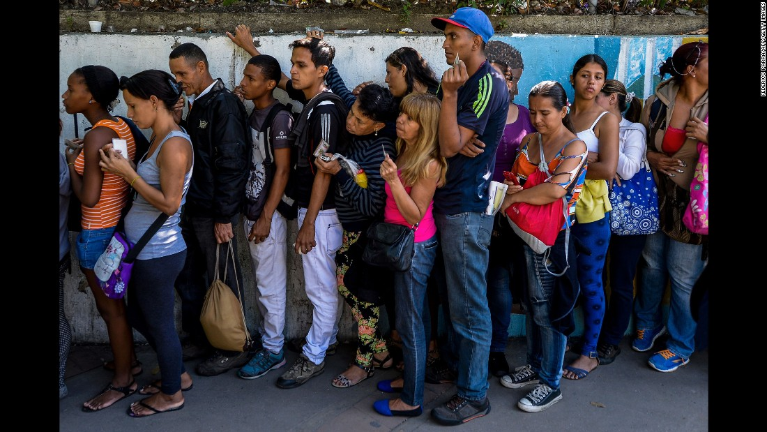 People queue to buy basic food and household items outside a supermarket in Caracas, on September 28.