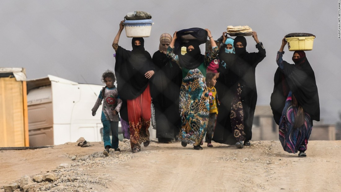 Iraqi families walk at a camp for displaced people near Qayyara on Monday, October 24.