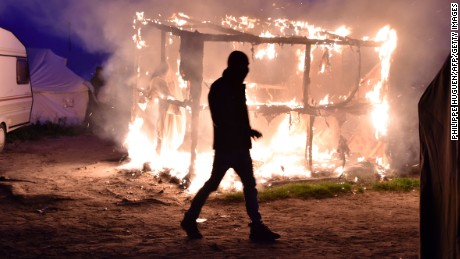 A migrant walks past a shack set ablaze on Tuesday night.