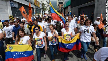 Lilian Tintori, wife of prominent jailed opposition leader Leopoldo Lopez, holds a Venezuelan flags as she marches.