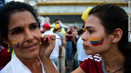 Women paint Venezuelan national flags on their faces during the march.