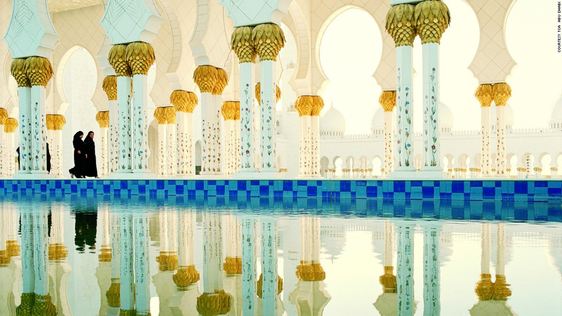 A 24-carat gold chandelier hangs in the main prayer hall of the Sheikh Zayed Grand Mosque and the walkways are lined by mirror pools amplifying its golden details.