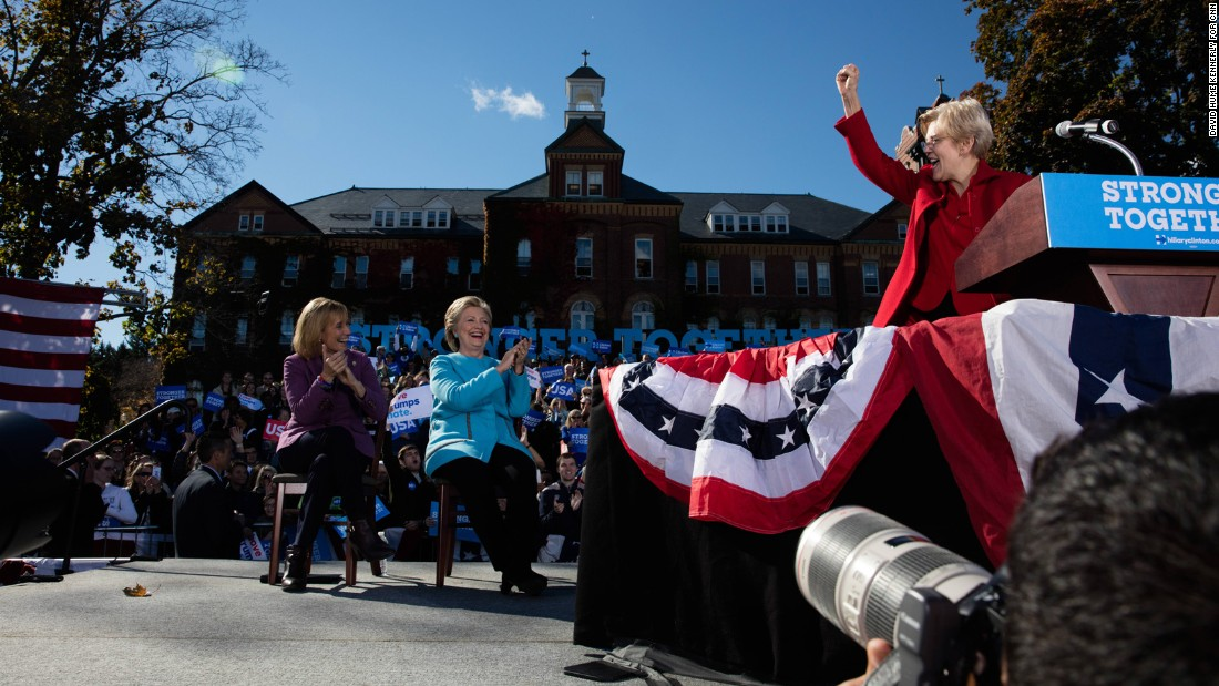Clinton, center, claps for US Sen. Elizabeth Warren at a rally in Manchester on October 24.