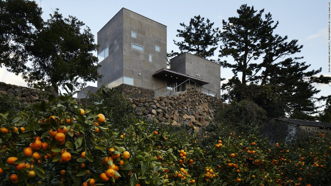 "Found on the South Korean island of Jeju, this concrete and volcanic-stone house was built on a citrus farm. It has a bowed roof that nods to the island's traditional housing, while maintaining an interconnected relationship with the outside. ""A house in Korea needs to respond to the changing weather,"" says architect Doojin Hwang. ""The interior becomes the exterior and vice versa."""
