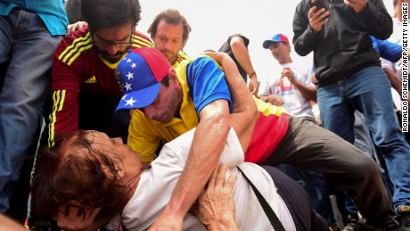 Leading opposition figure Henrique Capriles (C) assists a supporter during a demonstration against the government of Venezuelan President Nicolas Maduro in Caracas on October 26, 2016.