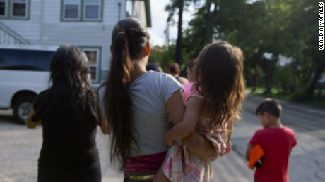A mother and her children walk outside the refugee house they stayed in after being released from detention
