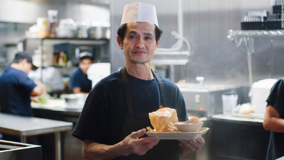 "Ming Ng, a cook at Mamak Malaysian restaurant in Houston, holds the roti canai dish. It's ""crispy on the outside, fluffy on the inside,"" the menu says."