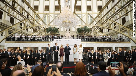 Donald Trump (C) and his family (L-R) son Donald Trump Jr, son Eric Trump, wife Melania Trump and daughters Tiffany Trump and Ivanka Trump prepare to cut the ribbon at the new Trump International Hotel October 26, 2016 in Washington, DC.