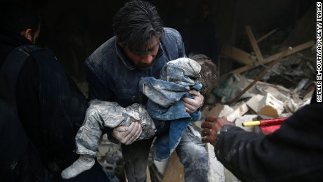 A Syrian man rescues a child after an airstrike in Douma in January.