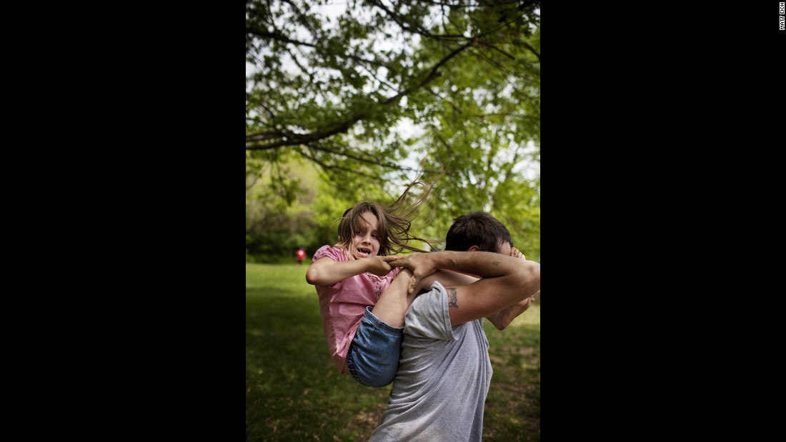 One of the twins slips off her father's shoulders as they play in Athens, Ohio, in 2009. Eich's college assignment was to document a community through photos. He found one with tenacity, intimacy and love, even in the depths of loss and poverty.