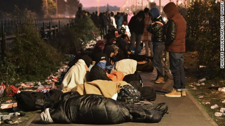 "TOPSHOT - Migrants who slept outside an aid station queue to be assigned to one of the processing centres across France, near the ""Jungle"" migrant camp in Calais, northern France, on October 27, 2016, during a massive operation to clear the squalid settlement where 6,000-8,000 people have been living in dire conditions. / AFP / PHILIPPE HUGUEN        (Photo credit should read PHILIPPE HUGUEN/AFP/Getty Images)"