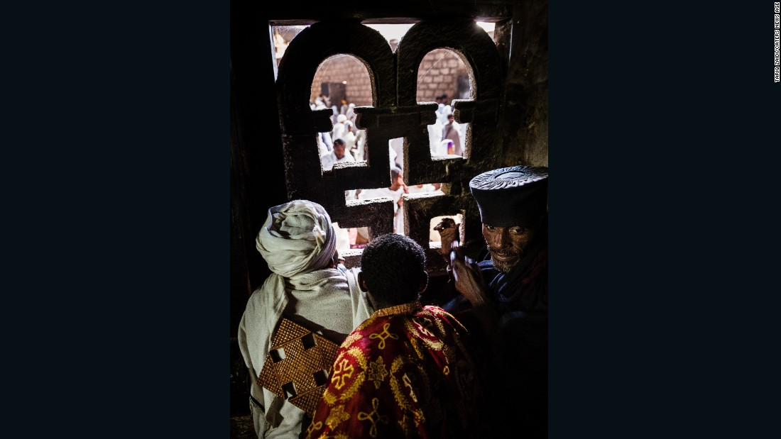 Here the priests of Lalibela look out of an intricately carved window of their church to the crowds below. Every church in Lalibela has a resident priest who wears ornate brocade robes and carries a large processional cross.