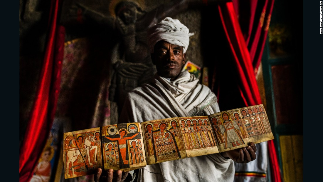 A priest from a church in Lalibela shows off an illuminated manuscript depicting Jesus, St George and other religious figures. Behind him is an intricate crucifix carved out of stone. The 13 churches of Lalibela are home to some of Ethiopia's most sacred artifacts.
