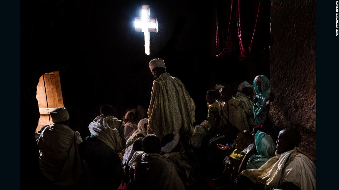Pilgrims wait inside a darkened room, praying, meditating, chanting or singing. Light streams in through a hand-carved cross in the wall.