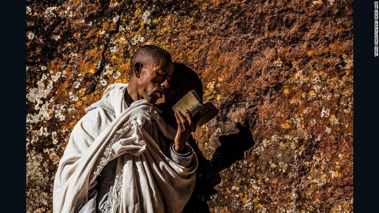 A pilgrim reading a bible and pressing his cheek to the holy walls of a church at Lalibela.