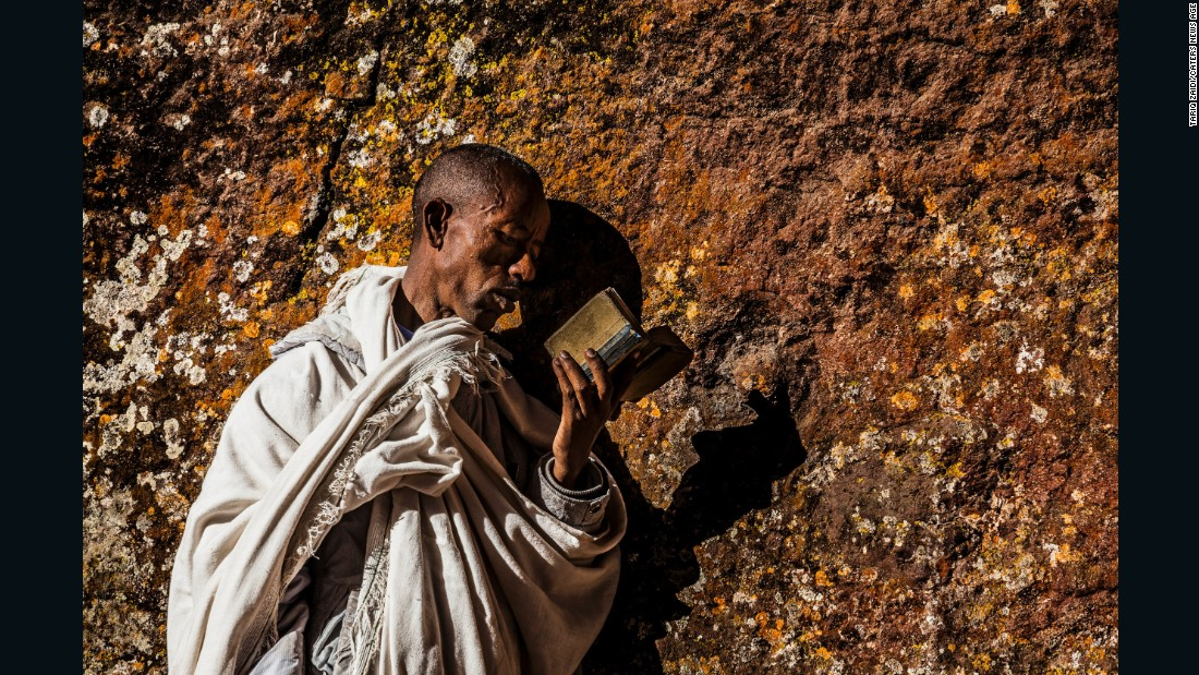 A pilgrim reading a bible and pressing his cheek to the holy walls of a church at Lalibela. Up to 100,000 pilgrims travel to this devotional site every year, many of them on foot and without shoes.